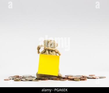 La bolsa de dinero y monedas con etiqueta de color amarillo sobre fondo blanco con espacio de copia.