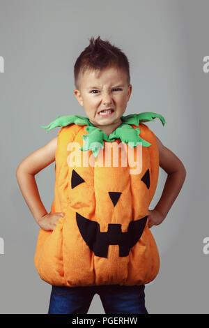 Retrato de adorables gracioso muchacho caucásico blanco vestido de calabaza de Halloween. Niño jugando a divertirse haciendo caras en studio para otoño otoño seaso