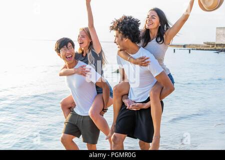 Grupo de amigos caminando por la playa, con los hombres que piggyback ride para novias. Feliz jóvenes amigos disfrutando de un día en la playa