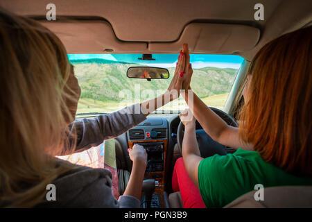 Hombre y mujer en el interior del automóvil y comer pastel de la carretera entre campos país marrón con hierba y montañas nevadas . Sol está brillando. Shoot f Foto de stock