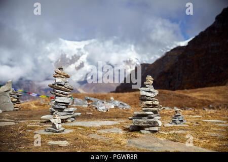 Pequeños montones de piedras en el Mardi Himal trek y nublado picos de las montañas del Himalaya en Nepal