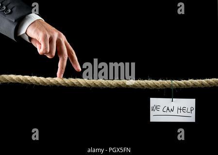 Concepto podemos ayudar con una nota escrita a mano con las palabras colgando de un hilo de una cuerda suspendida sobre un fondo negro con un empresario a pie