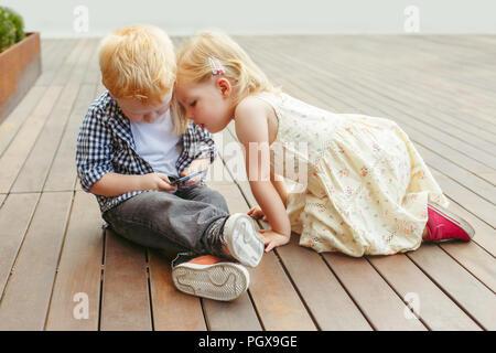 Dos cute adorable niños caucásicos blancos chico y chica sentados juntos y jugar juegos en los teléfonos móviles tableta digital. Estilo de vida sincero temprano