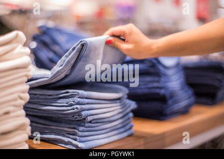 El tema de fondo de venta comercial. En el colgador de ropa jeans en la tienda.