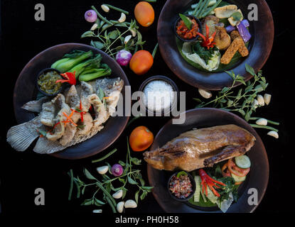 Muchos platos distintos vista desde arriba. El pescado, pato, chiken sobre fondo oscuro