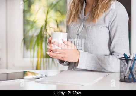 Mujer de negocios sentada en su escritorio en la oficina moderna y blanca sosteniendo una taza de café en la mano. Niña viste camisa elegante en tiras. Gran borrosa verde de windows