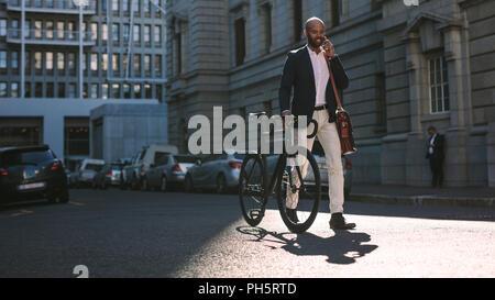 Joven Empresario de caminar al aire libre con una bicicleta y utilizando un teléfono móvil. Hombre africano para ir a trabajar en bicicleta hablando por teléfono celular en las calles de la ciudad.