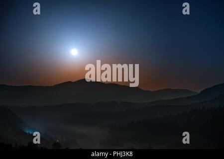 Moon rising por encima de las montañas en la noche Foto de stock