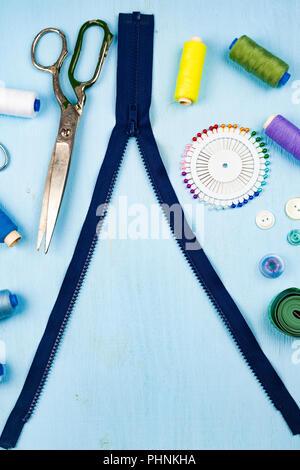 Zipper Unbuttoned y accesorios de costura sobre un fondo de madera azul. Cinta métrica, alfileres, botones, zipper, tijeras e hilo.
