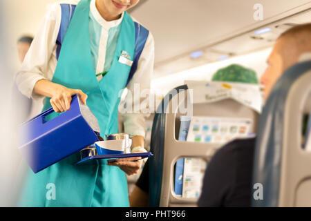 Azafata sirviendo bebidas a los pasajeros a bordo.