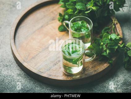 Té de menta herbal caliente en jarras de vidrio con hojas