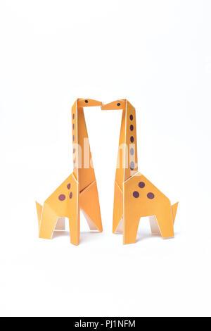 Dos jirafas beso origami amarillo sobre un fondo blanco.