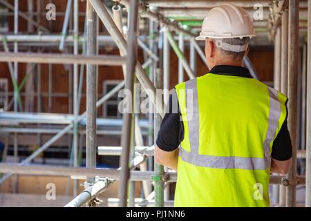 Vista trasera del generador de macho, trabajador de la construcción en el sitio de construcción vistiendo casco y chaleco de alta visibilidad