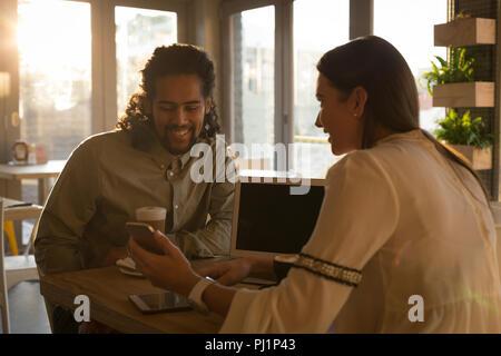 Pareja discutiendo sobre un teléfono móvil en el cafe Foto de stock