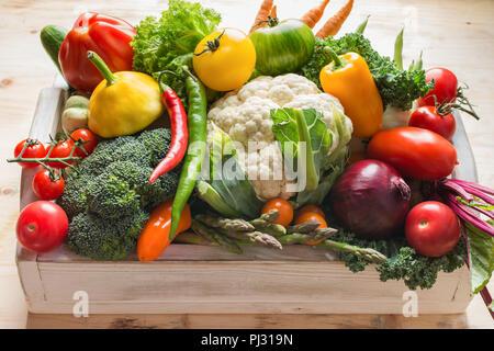 Coloridos vegetales orgánicos frescos en una bandeja de madera blanca en tabla de pino, de cerca, el enfoque selectivo