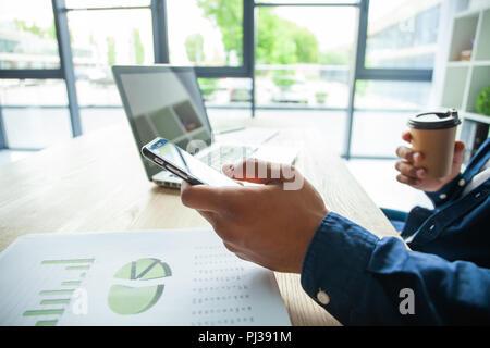 Feliz empresario afroamericano utilizando un teléfono móvil en una oficina.