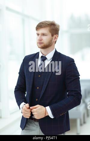 Pensativo joven empresario de pie cerca de la ventana de la oficina