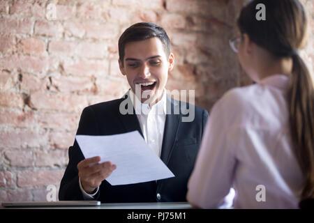 Trabajador feliz con el papel en la mano en el lugar de trabajo