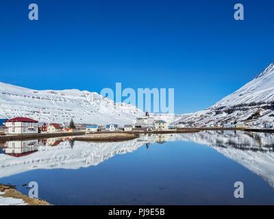 11 de abril de 2018; Seyðisfjörður Anuncios, Oriente Islandia - El pueblo se refleja en el fiordo, y el la línea de ferry Smyril MS Norrona.