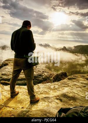 Fotógrafo doblar la cabeza comprobar la pantalla de la cámara. El hombre permanecer en Cliff y toma fotos. Hermoso paisaje de otoño misty misty amanecer en el horizonte