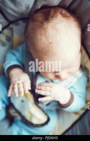 Retrato de cute adorable caucásicos blancos dormir poco Baby Boy nacido en azul ropa sentada en mecedora, vista de la cabeza manos desde arriba abo