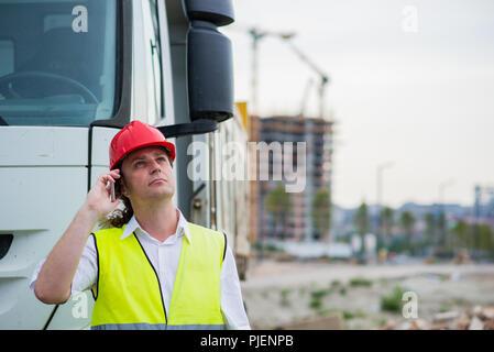El conductor del camión hablando por su teléfono móvil en un sitio en construcción Foto de stock