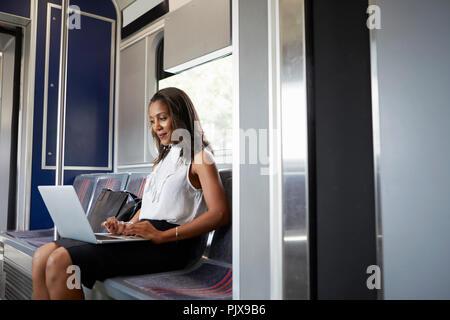 La empresaria utilizando el portátil en el tren