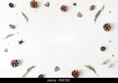 Composición decorativa de Navidad. Marco floral de evergreen juniperus ramas, hojas de eucalipto, pino, alerce y conos de confeti brillantes estrellas. Fondo de la tabla de madera blanca. Patrón de botánica.