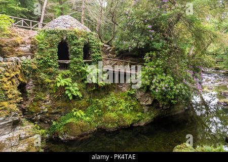 La ermita y el río, la Ermita En Tollymore Park, es un bonito refugio de piedra cubierto de hiedra en un paseo junto al río Shimna
