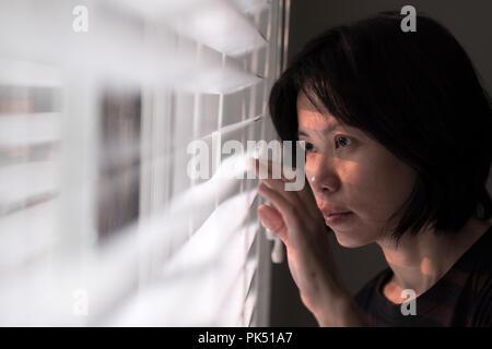 Retrato de joven mujer asiática que sobresale de la ventana