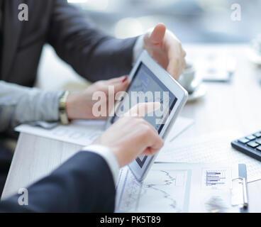 Close up.Equipo empresarial discutiendo gráficos financieros mediante tableta digital.