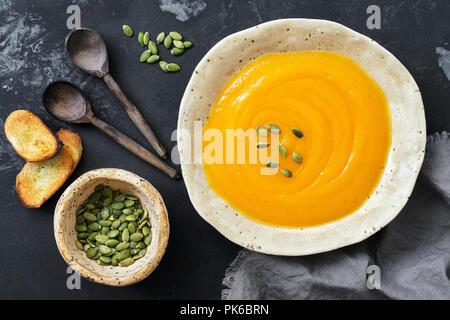 Sopa crema de calabaza con tostadas y semillas sobre un fondo oscuro y rústico. Vista superior, sobrecarga, plano laical.