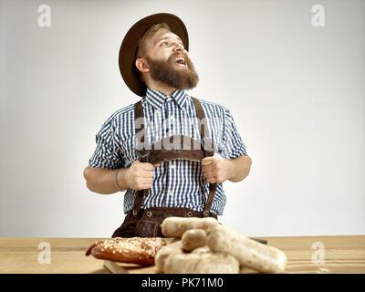 Alemania, Baviera, la Alta Baviera. El joven hombre sonriente con cerveza vestida con traje tradicional bávaro austriaco o en hat sentado en la tabla en el studio