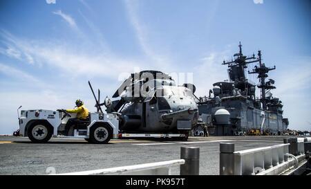Mar de Mindanao - Marines con medio marino Tiltrotor squadron (VMM) 166 reforzado, 13ª Unidad Expedicionaria de los Infantes de Marina (MEU), y los marineros de la Marina de los EE.UU con el Essex Amphibious Ready Group (ARG) mover un tipo CH-53E Super Stallion desde VMM-166 en posición para el despegue a bordo de la clase Wasp buque de asalto anfibio USS Essex (LHD 2), durante las operaciones de búsqueda y salvamento de la falta de un Marine adjunta a la 13ª MEU mientras en un despliegue programado regularmente de la Essex ARG y 13ª MEU, 12 de agosto de 2018, 12 de agosto de 2018. El Essex ARG/ 13 MEU está desplegada actualmente en la séptima Flota de la zona de operaciones. (U.