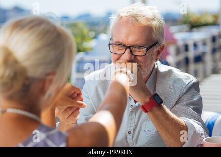 Alegre anciano sosteniendo su mano wifes