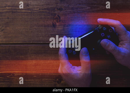 Hombre jugando juegos de video juegos PlayStation® controller en madera con luces de fondo