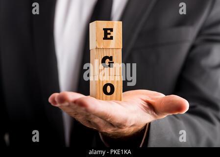 Empresario celebración bloques de letras de madera de leer - Ego - equilibrado en la palma de su mano en una imagen conceptual.
