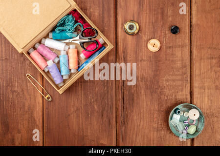 Una fotografía aérea de una caja de costura con hilos, agujas y tijeras, con un pasador de vintage, botones y copiar el espacio, disparó desde arriba en un oscuro rústico b