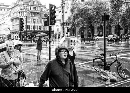 El 24 de agosto de 2018 - Londres, Inglaterra. Imagen en blanco y negro de un grupo de personas atrapadas en el mal tiempo. Una mujer cubriendo con grandes viejo libro de la
