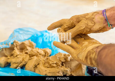 Artista Masculino limpieza de la arcilla en sus manos.