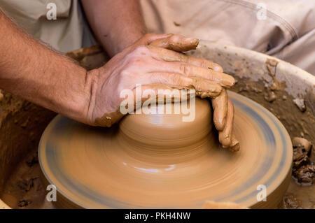 Cerrar las manos de un hombre joven trabajando en un torno de alfarero
