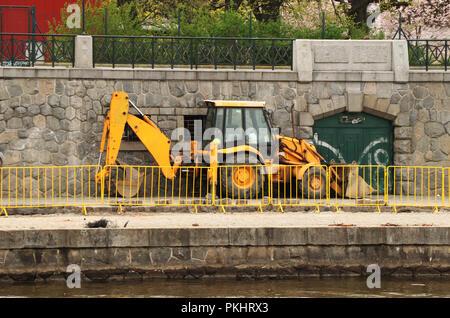 Un tractor amarillo en Praga costa para la construcción de pavimento nuevo en la ciudad. La capital y la reparación de los antiguos pavimentos