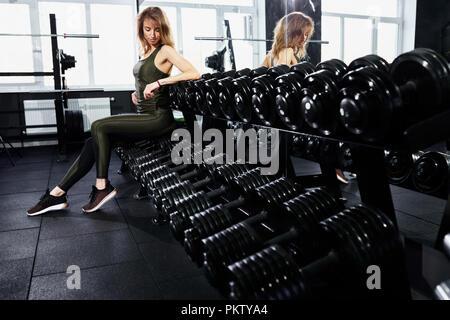 Joven rubia niña sentada sobre una pesa en el gimnasio cerca del espejo