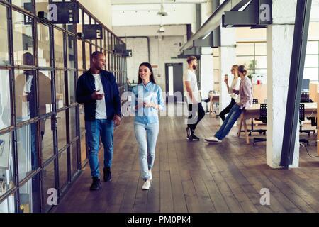 Captura hasta antes de la reunión. La longitud completa de la joven la gente moderna en smart ropa casual discutir negocios y sonriendo mientras camina por el pasillo de la oficina.