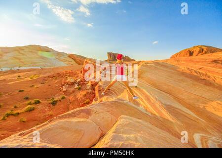 Turismo joven chica saltando por ola de incendios en el Valle de Fuego, Nevada, EE.UU., en el rojo atardecer. Excursionista feliz disfrutando la vista de populares líneas de rayas alrededor del labio de la ola de incendios. La roca de Gibraltar en segundo plano.