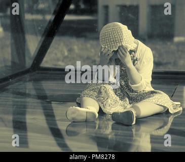 Muy realista, parecido a una muñeca llorando poco chica sentada detrás de un vidrio exterior de estilo vintage de la imagen en blanco y negro con un espacio de copia