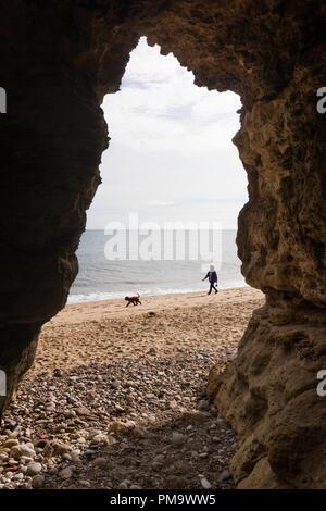 Mujer paseando a un perro, a lo largo de la playa enmarcada por una cueva, Seaham, Condado de Durham, Inglaterra, Reino Unido.