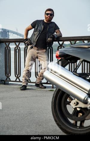 Pelirroja biker con barba en chaqueta de cuero recostado en barandillas cerca de moto en el puente