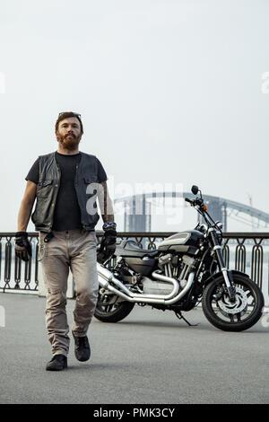Pelirroja biker con barba en chaqueta de cuero de pie caminando sobre el puente cerca de moto