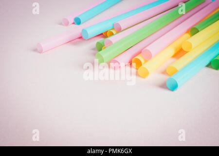 Pajas de plástico multicolor sobre fondo de color rosa